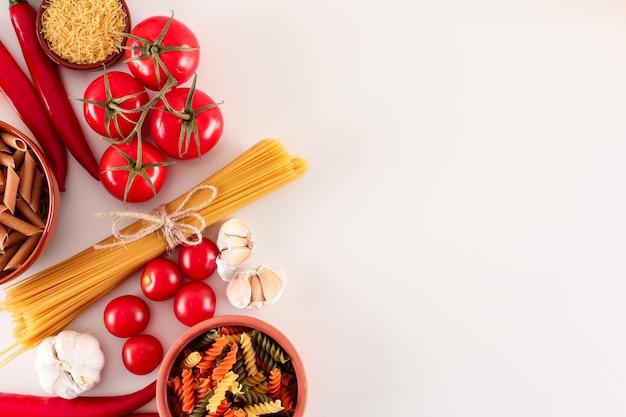 Сырые спагетти и цветные макароны и помидоры с копией пространства на белой поверхности