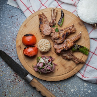 Вид сверху на шашлык с жареными овощами и нарезанным луком, ножом и айраном в деревянном подносе.