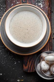 白い皿にシャンピニオンのトップビューキノコスープ