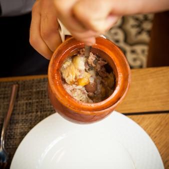 白い皿とフォークと粘土の水差しで人間の手でトップビューピティ