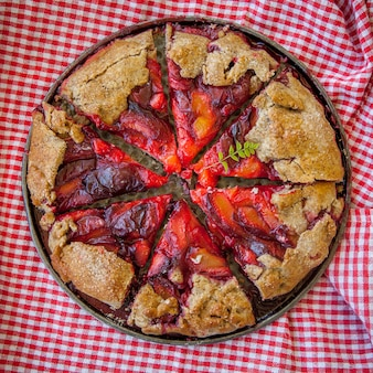 オーブン鍋に市松模様のぼろきれと上面のイチゴのパイ