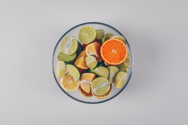 Лимоны с зелеными лимонами и апельсином в шаре на белой предпосылке, взгляд сверху.