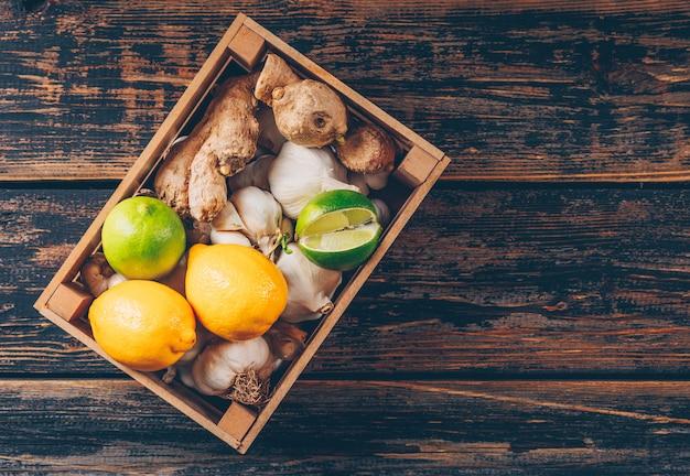 Плоские лежал зеленый и желтый лимоны в деревянной коробке с имбирем, чесноком на фоне темных деревянных. горизонтальное пространство для текста