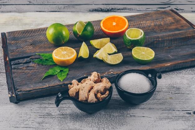 Зеленые и желтые лимоны и апельсин с чашки соли и имбирь вид сбоку на деревянный поднос и серый деревянный фон
