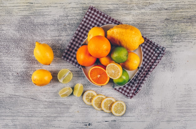 Апельсин с зелеными и желтыми лимонами с кусками в плите на ткани и серой деревянной предпосылке, взгляд сверху.