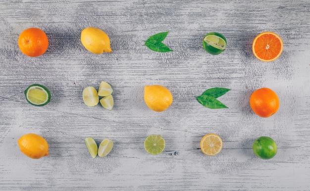 Набор зеленых и желтых лимонов и апельсина с кусочками на сером фоне деревянных. вид сверху.