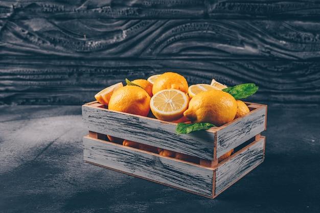 スライスと黒の織り目加工の背景に葉のついた木箱に側面図レモン。横型