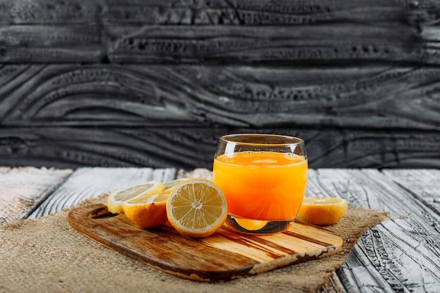 まな板、布、木製の背景にスライスとジュースとレモンの側面図です。テキストの水平方向のスペース