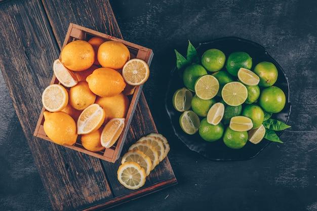 Лимоны взгляд сверху в деревянной коробке с зелеными лимонами и кусками на деревянном подносе и черной текстурированной предпосылке. горизонтальный
