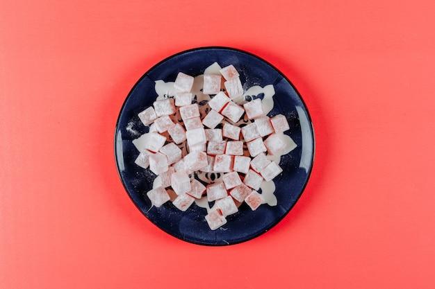 Вид сверху лукум лукумы в тарелку на светло-красном фоне. горизонтальный