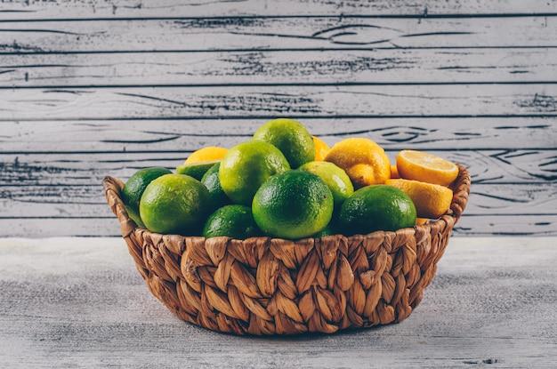 Желтые и зеленые лимоны в виде сбоку корзины на сером фоне деревянных