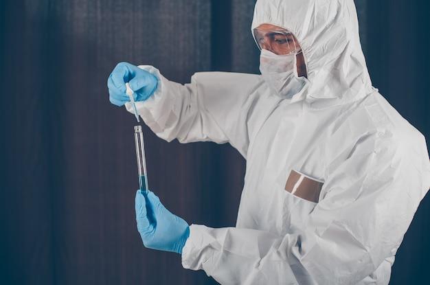 Портрет доктора, берущего образцы лекарств с маской, перчатками и защитным костюмом