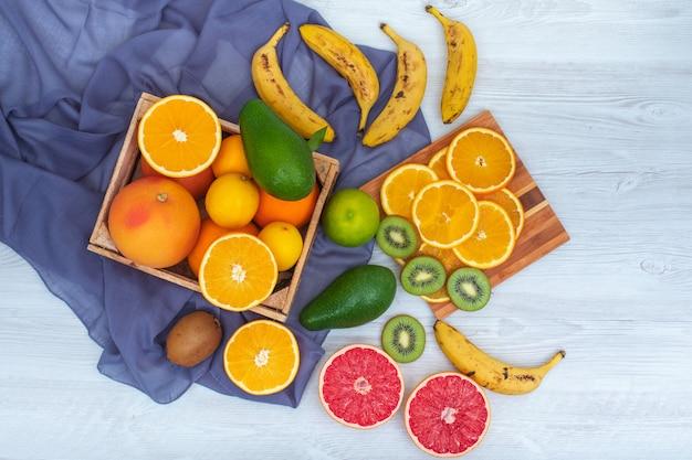 白い布の表面に青い布と木製のまな板に柑橘系の果物のトップビュー