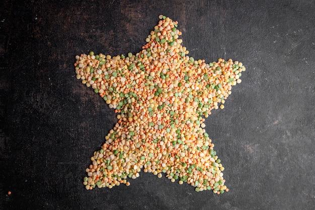 レンズ豆は暗い織り目加工の背景に星の形を形成します。上面図。