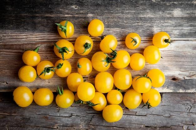 暗い背景の木に黄色いトマト。上面図。