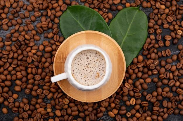 Кофейная чашка и кофейные зерна на черной поверхности вид сверху