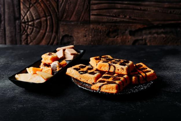 クッキー、黒のテクスチャと木製の背景にオレンジ色のプレートで高角度のビューワッフル。横型