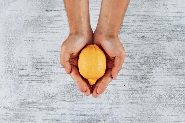 明るい木製の背景に彼の手の上面に緑のレモンを抱きかかえた