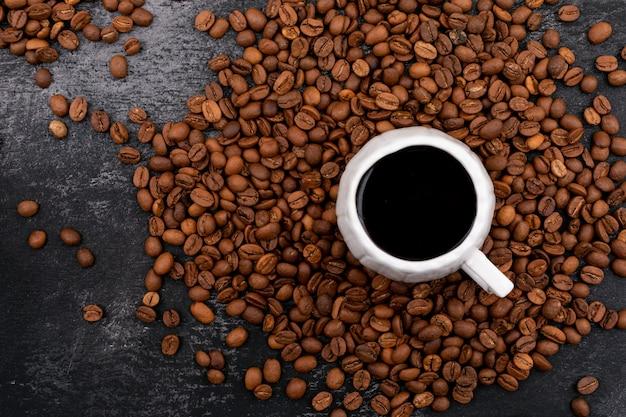 Чашка кофе в окружении кофейных зерен на черной поверхности