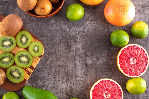 キウイフルーツグレープフルーツアボカドとオレンジフルーツトップビューで黒い表面にコピースペース