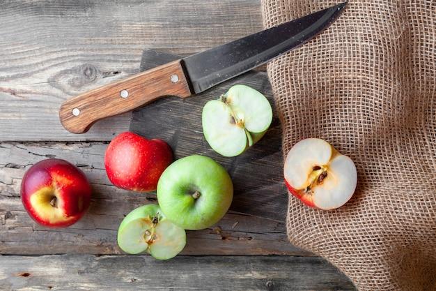 Зеленые и красные яблоки разрезать пополам с ножом, дерева и ткани вид сверху на темном деревянном фоне