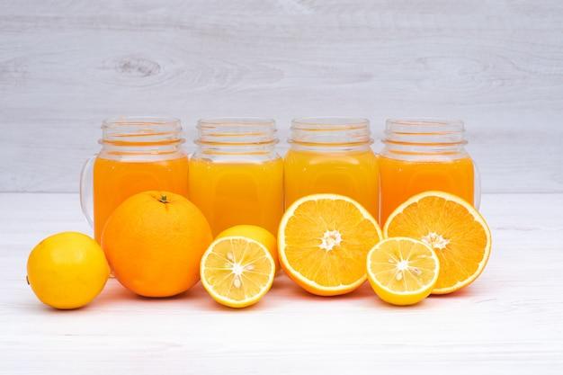白いテーブルの上のグラスにレモンとオレンジジュース