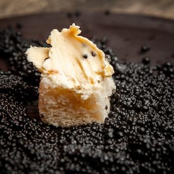 暗い背景にパンとバターとブラックキャビアのセット。ハイアングル。