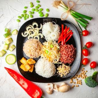ねぎと赤唐辛子と白いテクスチャ背景に黒い皿でおいしい食事のセット。上面図。