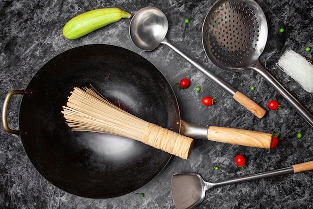 キッチンツールと黒の織り目加工の背景にフライパンのセット。上面図。