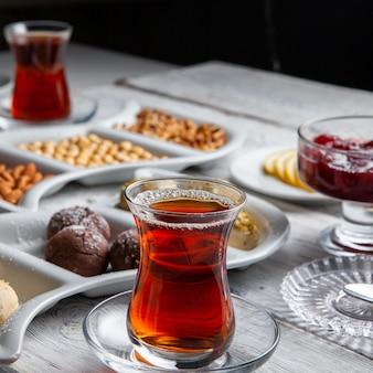 お茶、ナッツ、フルーツジャム、白い木製の背景においしいデザートのセット。ハイアングル。