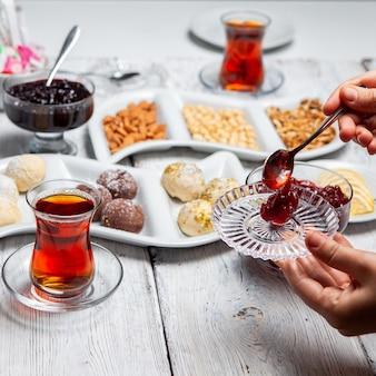 Набор чая, орехов, фруктового джема и вкусных десертов на белом фоне деревянные. высокий угол обзора.