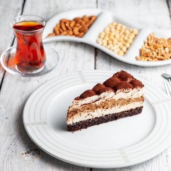 Набор чая, орехов и вкусный десерт в тарелку на белом фоне деревянные. высокий угол обзора.