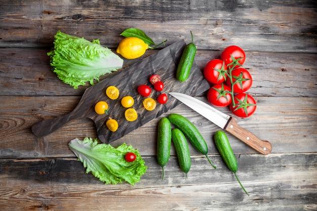 Комплект томатов, салата, лимона и ножа и огурца в разделочной доске на темной деревянной предпосылке. вид сверху.
