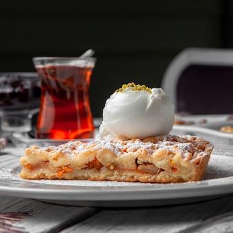 Десерт взгляда со стороны в плите с чаем на белой деревянной и черной предпосылке.