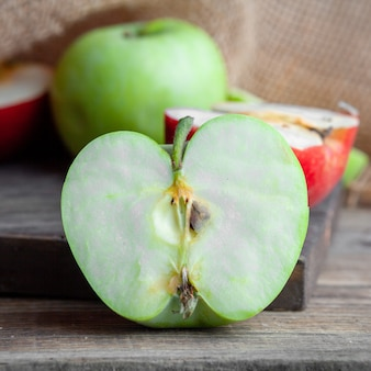 側面図の緑と赤のリンゴは、木材、布、暗い背景の木の上を半分にカットしました。横型