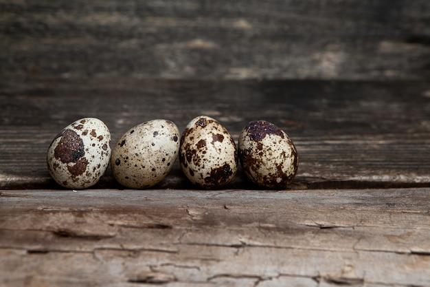Некоторые перепелиные яйца на фоне темных деревянных, вид сбоку. свободное место для вашего текста