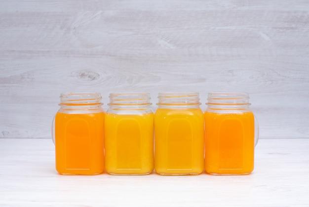 Апельсиновый и лимонный сок в очках на белом столе