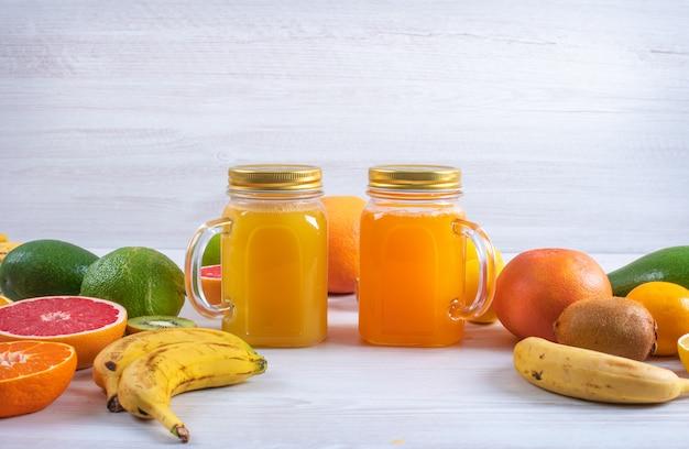 白いテーブルに異なるカラフルな新鮮な柑橘系の果物に囲まれたオレンジとレモンジュース