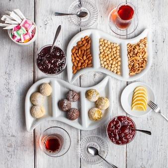 Вид сверху вкусные десерты с чаем, орехами, фруктовым джемом на белом фоне деревянные.