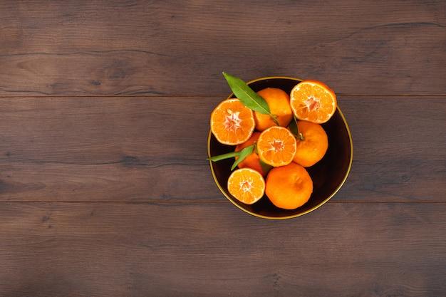 茶色の表面にボウルに葉とオレンジ色の果物