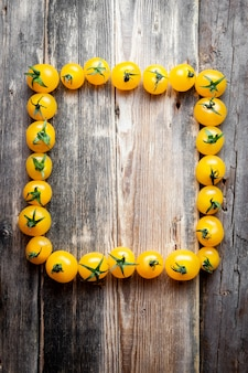 Желтые томаты формируя рамку прямоугольника на темной деревянной предпосылке. вид сверху.