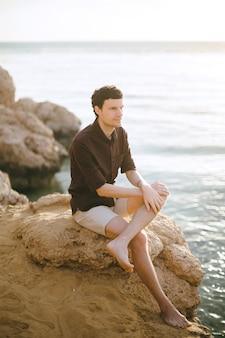 岩の上に座って、昼間に海岸で遠くを見て黒いシャツを着たハンサムな男。