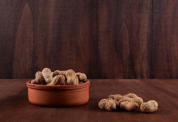 Вид сбоку арахис в миске на горизонтальном