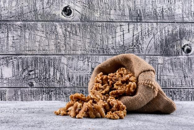 Вид сбоку грецкие орехи в мешок на каменный стол горизонтальный