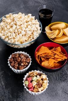 Вид сбоку чипсов и попкорна в мисках на черной вертикали