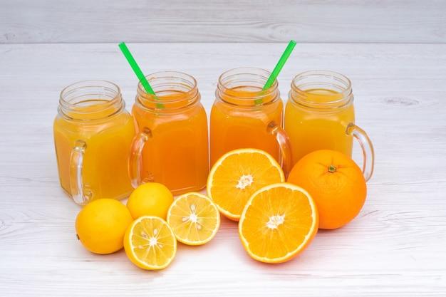 白い木製のテーブルにおいしいオレンジとレモンジュース