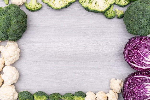 白い木製の表面にコピースペースを持つカラフルな野菜ブロッコリーカリフラワー赤キャベツのフレーム