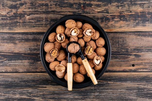 Вид сверху грецкие орехи и щелкунчик в плите на деревянном столе горизонтальном