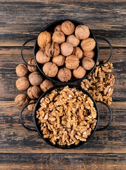 Вид сверху грецкие орехи в корзинах на деревянной вертикали