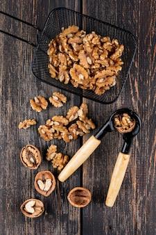 Вид сверху грецкие орехи в черной корзине с щелкунчиком на деревянной вертикали